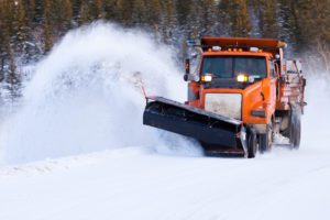 Snow plow clearing snow-covered road